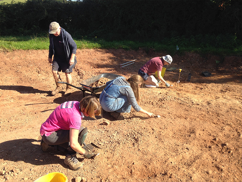 Three people digging carefully